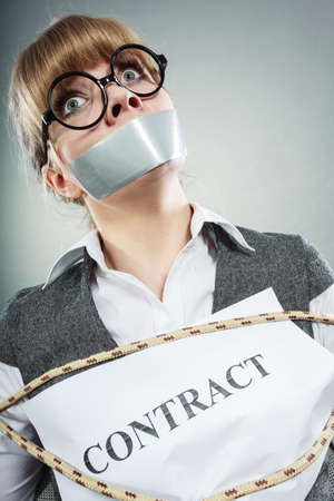 slave: Afraid businesswoman bound by contract terms and conditions with mouth taped shut. Scared woman tied to chair become slave. Business and law concept. Stock Photo