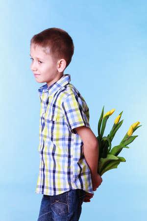 ocasiones especiales de vacaciones y día de la madre. El muchacho joven preparar flores de regalo sorpresa sostienen tulipanes detrás de la espalda.