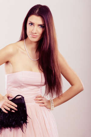 strapless: Beauty, fashion and elegant people concept - young brunette slim woman in bright strapless dress holds black clutch bag Stock Photo