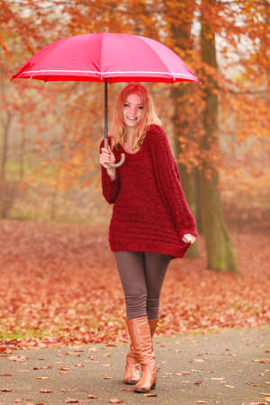 Smiling happy fashion cute woman girl in maroon sweater with umbrella relaxing in fall autumn park. Happiness and relax in forest.