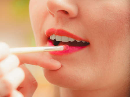 visagiste: Make up artist applying lipstick with brush on woman lips. Closeup of visagiste and girl. Beauty and makeup concept. Stock Photo