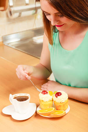 glutton: Woman with cup of coffee forking delicious gourmet sweet cream cake cupcake and orange. Glutton girl sitting in kitchen with hot beverage having breakfast. Appetite and gluttony concept. Stock Photo