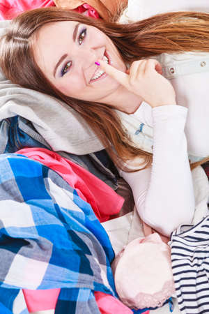 mess: Portrait of happy glad young woman girl lying on stack of clothes with finger on lips asking for silence. Disorder and mess. Stock Photo