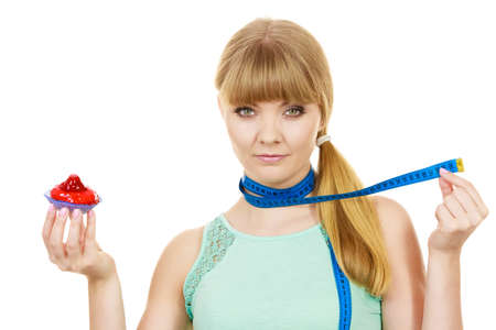 overeat: Woman undecided with blue measuring tape around her neck holds in hand cake cupcake, trying to resist temptation. Weight loss diet dilemma gluttony concept.