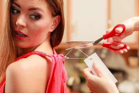 price cutting: Woman girl removing cutting label board price tag off new dress cloth with scissors. Female after shopping. Stock Photo
