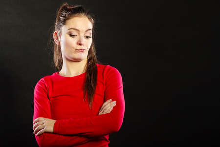 wistful: Portrait of pensive thoughtful woman. Attractive young girl thinking in studio on black. Stock Photo
