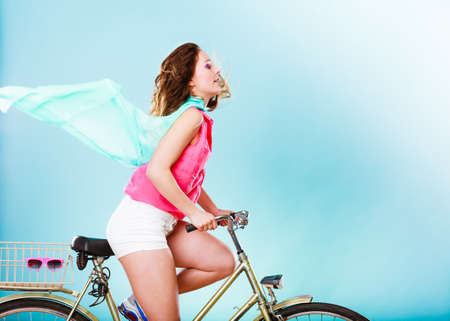 active: Active woman riding bike bicycle fast against wind. Young girl with hair windblown. Healthy lifestyle and recreation leisure activity. Studio shot.