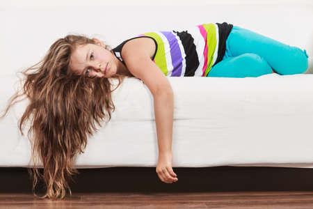 Niña perezosa agotada cansada acostada en el sofá en casa. Niño soñoliento descansando relajándose en el sofá.