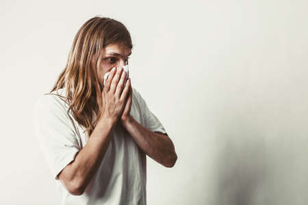 long nose: Allergy and cold concept. Young long haired sick man with hygienic tissue. Guy blowing nose.