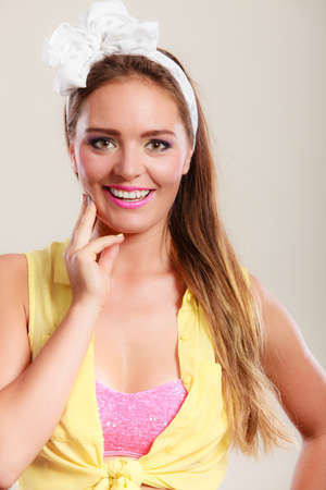 hairband: Portrait of happy smiling pretty pin up girl with hairband bow. Attractive gorgeous young retro woman posing in studio.