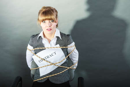 bound woman: Afraid businesswoman bound by contract terms and conditions. Terrified scared woman tied to chair become slave. Business and law concept.