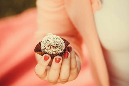 small cake: Food and sweets. Appetite and tasty meal dessert. Part body woman with little cookie cupcake. Hand holding small cake.