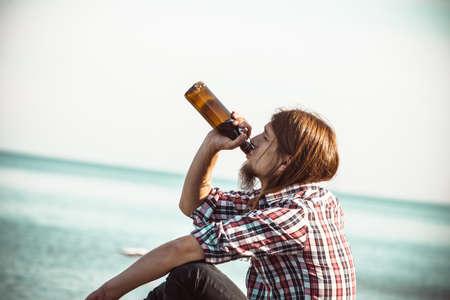 alcoholismo: Hombre deprimido con la botella de vino sentado en la playa al aire libre. La gente abuso y problemas de alcoholismo