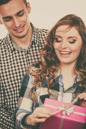 male bonding: Couple and holiday concept. Smiling young man surprising cheerful woman with pink gift box