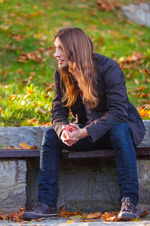 man with long hair: Man long hair sitting on bench outdoor in autumnal park, relaxation
