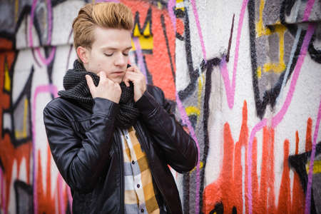 handsome trendy man outdoor in city setting, male model wearing black jacket scarf and checked shirt against colorful graffiti wall Stok Fotoğraf