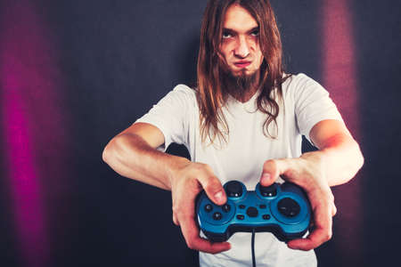 xbox: Addiction. Stressed depressed young man playing gaming on pad. Angry guy with controller pad play console. Face expression.
