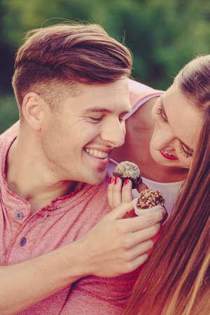 Liebe und Glück. Nette reizende Liebhaber, die sich durch kleine Kuchenplätzchen füttern. Lächelndes Paar mit süßem Essen, das Spaß hat.