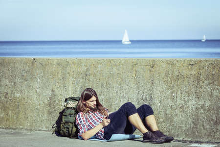 tramping: Man tourist backpacker relaxing outdoor sitting by grunge wall using tablet. Internet, tourism active lifestyle. Young hipster guy tramping