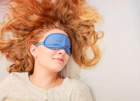 sleep mask: Tired woman sleeping in bed wearing blindfold sleep mask. Young girl taking nap.