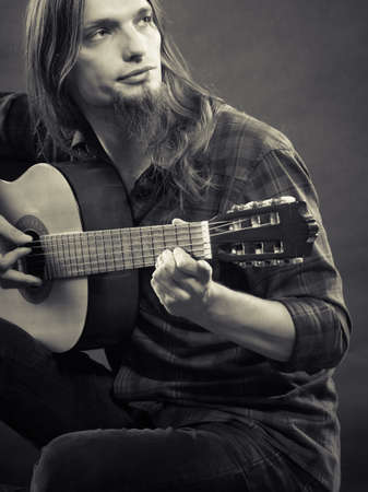 guy playing guitar: Hobby relax art concept. Man bearded guy playing guitar black & white photo