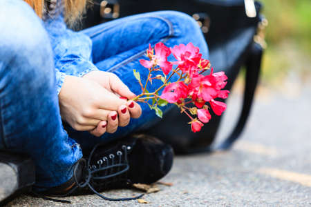 sitting on the ground: Lifestyle and leisure. Part body woman with beautiful pink flower sitting on ground. Modern fashionable girl wearing jeans clothes spends time on fresh air.