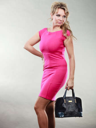 Fashion of women. Clothing and accessories. Mid aged blonde fashionable woman with handbag. Elegant lady in pink dress with black bag. 版權商用圖片 - 126093738