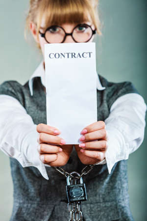 tied woman: Business concept. Serious woman businesswoman with chained hands holding contract, side view grungy background