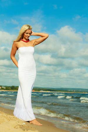 Toerisme en recreatie. Schoonheid aantrekkelijke vrouw lopen op de rand van de zee. Vrouwelijke toerist rustend op frisse lucht aan zee.