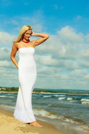 Turismo y recreación. Mujer atractiva de la belleza que camina en el borde del mar. Turista descansando sobre aire fresco en la playa.