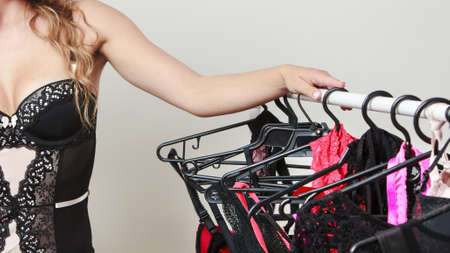 seductive women: Shopping for evening romance. Gorgeous attractive sexy woman buying lingerie. Seductive woman wearing black tempting underwear on shopping.