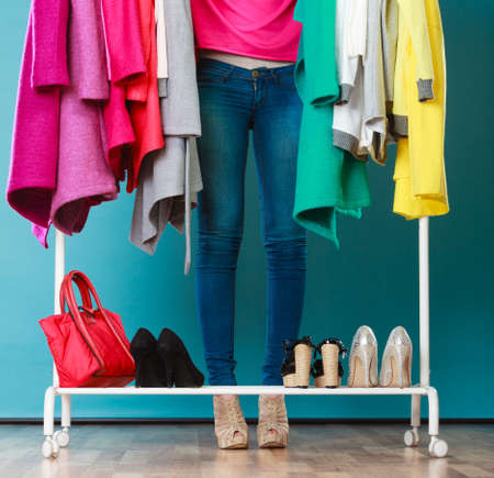 Closeup of woman choosing clothes to wear in wardrobe. Girl customer shopping in mall shop. Fashion clothing sale concept. Stockfoto