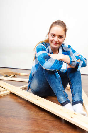enthusiast: Woman assembling wood furniture. DIY enthusiast. Young girl doing home improvement.