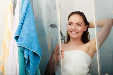 Girl showering in shower cabin enclosure. Woman taking care of hygiene in bathroom. Banque d'images
