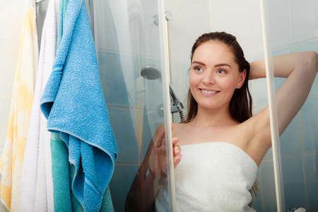 Niña de la ducha en el recinto de la cabina de ducha. Mujer que toma el cuidado de la higiene en el baño. Foto de archivo