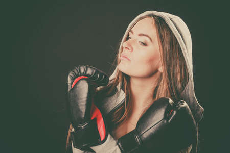 sportsmanship: Exercising prepare for fight. Sportsmanship and strong body. Side look young woman wear sportswear and boxing gloves. Stand with crossed hands wear hoodie.