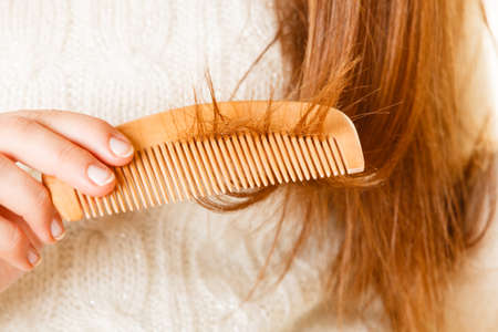 Female hand combing with brush her dry damaged long hair. Daily preparation for looking nice.