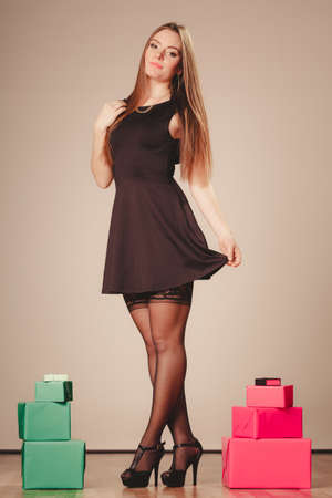 Helping and giving concept. Beauty gorgeous attractive sexy woman in black with boxes presents gifts lying on floor panels indoor.
