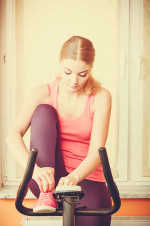 stationary bicycle: Active young woman on exercise bike stationary bicycle tying lacing shoes. Sporty girl training at home. Fitness and weight loss concept.