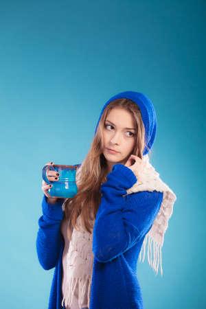 Hot beverage. Closeup teen girl holding blue mug with drink tea or coffee. Woman warming herself