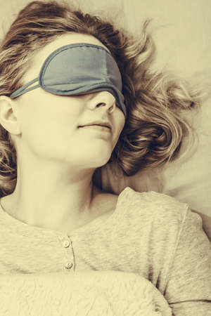 sleep mask: Tired woman sleeping in bed wearing blindfold sleep mask. Young girl taking nap. Sepia.