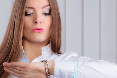 retardation: Time management. Beautiful woman showing the time on her wrist watch indoor