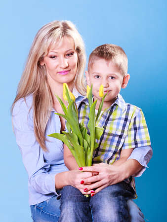 special occasions: Special occasions holiday and mother day. Young boy spend time with mother celebrate together give flowers gift.