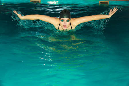 breath taking: Woman athlete swimming performing butterfly style stroke in pool. Active human swimmer taking breath. Water sport comptetition.