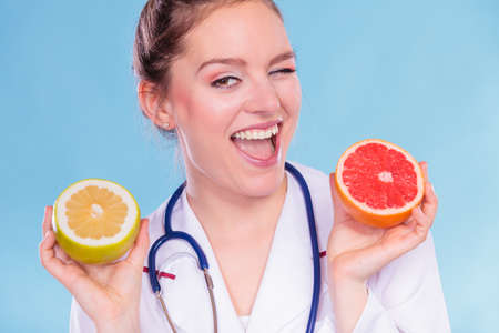 eating right: Happy dietitian nutritionist holding grapefruits. Woman promoting healthy food fruit. Right eating nutrition and slimming concept. Stock Photo