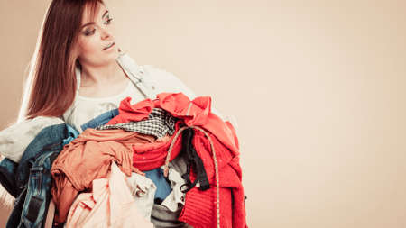 daily routine: Daily routine in household laundry wash and ironing. Young girl hold pile of colorful clothes.