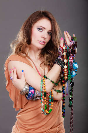 plentiful: Pretty young woman wearing bracelets and rings holding many plentiful of precious jewelry necklaces beads. Portrait of gorgeous fashion girl in studio on gray.