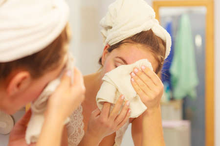 Woman cleaning washing her face with clean water in bathroom. Girl taking care of her complexion. Morning hygiene. Skincare treatment