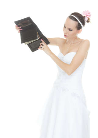 expenditure: Bride with empty wallet. Young girl holding purse looking for money cash. Wedding expenses costs, expenditure. Finance concept. Woman in white wedding dress isolated on white background.