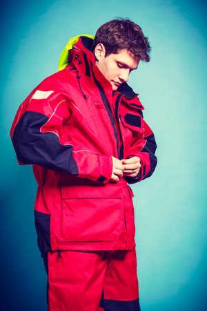 vistiendose: Varón joven que consigue vestido. El hombre en poner la ropa a prueba de agua. Aventura peligro al aire libre concepto.